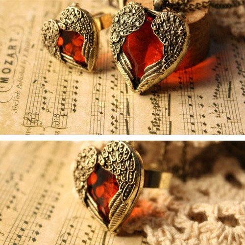 Ring mit Kopf in Herzform umrahmt mit Flügeln